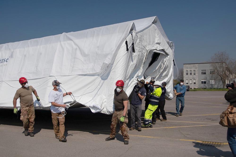Helfer tragen ein Zelt vom Notfallkrankenhaus